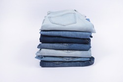 Closeup Lot of used different jeans stacked in a pile isolated on white background