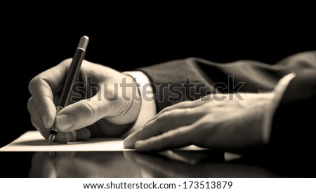 Closeup low angle perspective of a businessman in a suit signing a document with a fountain pen as he closes a business deal or finalises a contract or agreement #173513879