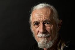 Closeup low key studio portrait of beautiful gray hair old man looking at the camera. Horizontally.