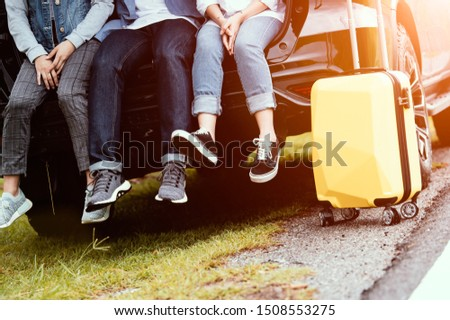 Closeup lower body of group of friends relaxing on SUV car trunk with trolly luggage along road trip with autumn mountain hill background. Freedom  road way. People lifestyle transportation travel