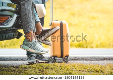 Closeup lower body of group of friends relaxing on SUV car trunk with yellow trolly luggage along road trip with mountain hill background. Freedom road way. People lifestyle and transportation travel
