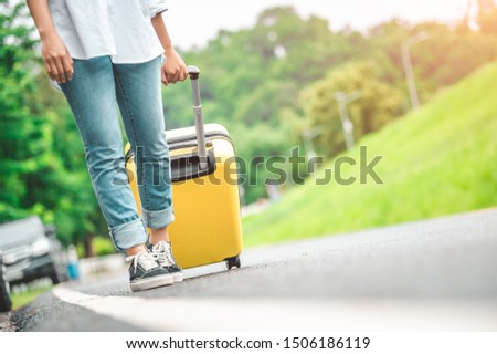 Closeup lower body of woman handling yellow trolly luggage along road trip with mountain hill background. Freedom girl on road way in summer. People lifestyles and transportation travel concept.