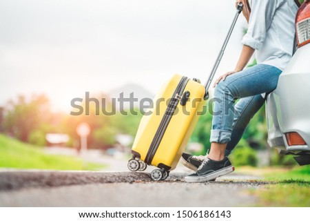 Closeup lower body of woman leg relaxing on car trunk with trolly luggage along road trip with autumn mountain hill background. Freedom road way. People lifestyle transportation travel in vacation