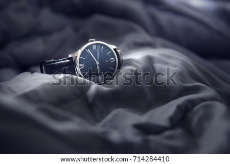 Closeup luxury man wrist watch black dial on gray fabric background. Dark toned.