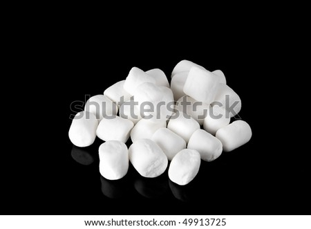 closeup macro of a small group of white mini marshmallows on a black plate