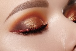 Closeup Macro of Woman Face with Gold glitter Eyes Make-up, bright red liner. Fashion Celebrate Makeup, Glowy Clean Skin, perfect Shapes of Brows. Shiny Simmer and metalic eye shadows