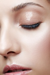 Closeup macro shot of female face and eyes beauty makeup. Woman with glossy glitter white skin.