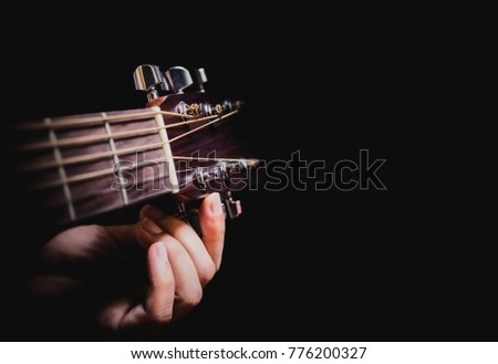 Stock Photo closeup male musician hands tuning acoustic guitar strings, isolated on black