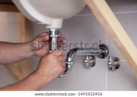 Closeup male plumber worker in blue denim uniform, overalls, fixing sink in bathroom with tile wall. Professional plumbing repair service, installation of water pipes, man mounted sewer drain