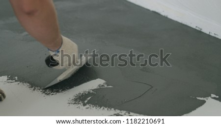 closeup male worker applying micro concrete plaster coating on the floor with a trowel