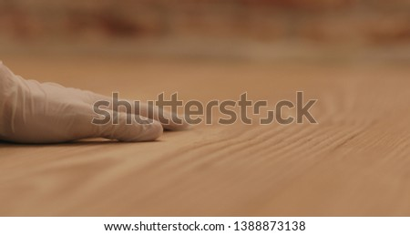 closeup man hand touches ash wood floor #1388873138