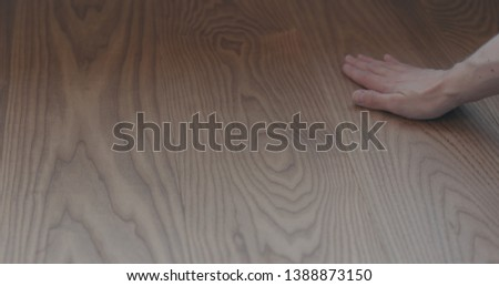 closeup man hand touches ash wood floor #1388873150