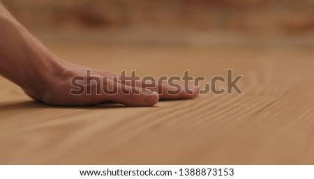 closeup man hand touches ash wood floor #1388873153