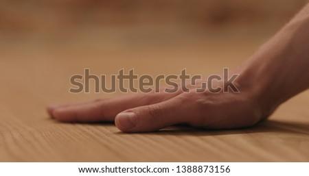 closeup man hand touches ash wood floor #1388873156