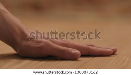closeup man hand touches ash wood floor #1388873162