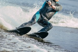 closeup man riding water skis on lake in summer. body parts without a face