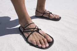 Closeup man's feet wearing primitive black sandals with string laces on white sand beach