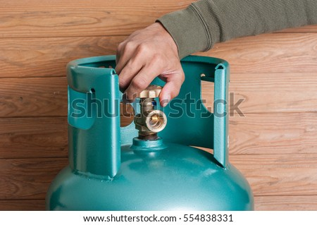 Closeup man's hand operating valve of LPG cylinder for cooking