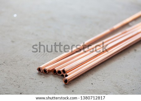 Closeup many new copper dyne pipes on the concrete floor. Concept installation, replacement of plumbing, repair of the pipeline, professional master plumber, leakage pipe #1380712817