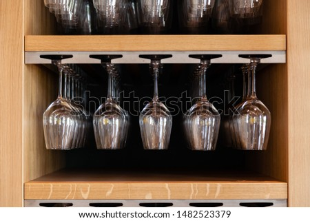 Closeup many upside down empty clear transparent crystal upturned wine glasses hanging in straight rows on brown wooden shelf, rack, showcase, stainless steel railing in bar, cabinet