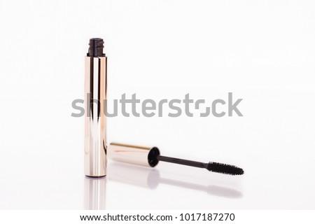Closeup Mascara Bottle and Brush. Black Mascara wand and Tube Isolated on White. Gold Bottle. Mascara on Light Background, New Form Brush. Mascara New Formula on white Background with Brush