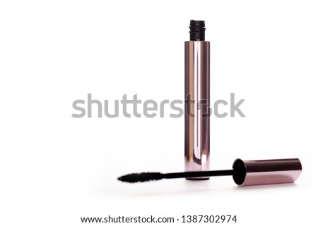 Closeup Mascara Bottle and Brush. Black Mascara wand and Tube Isolated on White. Gold Bottle. Mascara on Light Background, New Form Brush. open new mascara with a brush on white. - Image