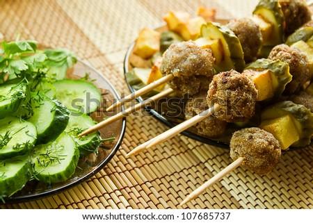 Closeup  meatballs kebab and  fresh cucumbers salad