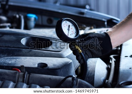 Closeup mechanic hands are holding pressure gauge, engine oil tester. Open hood with automobile motor on background. Repairer is repairing car at service station. Modern equipment for auto repair shop