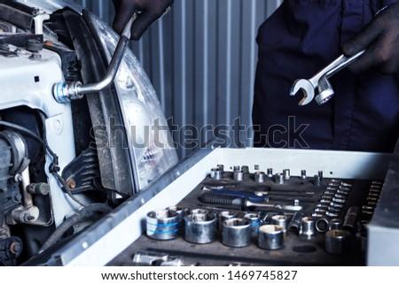 Closeup metal work tool of car mechanic at workshop auto repair shop. Repairman is choosing wrench for fixing vehicle. Repairer is repairing automobile at modern service station garage.