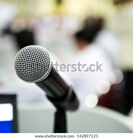 Closeup microphone in conference room with blur person.