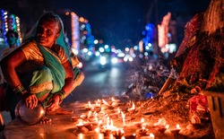 Closeup Middle-aged woman devotee offers prayers with incense stick on the night of Diwali outdoors. selective focus