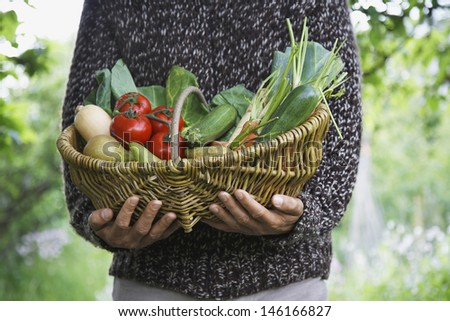 Closeup midsection of a man holding vegetable basket outdoors