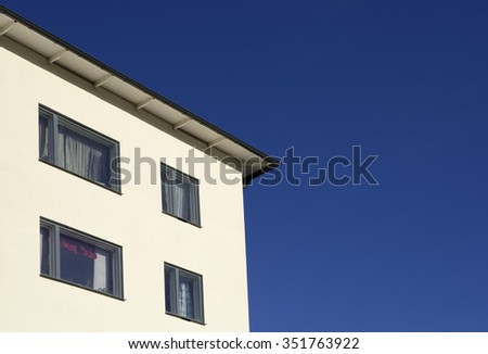 Closeup modern apartment building against blue sky. #351763922