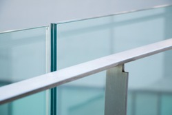 closeup modern flat stainless railing and glass wall on outdoor building.