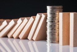 Closeup money coins heap stop the falling domino
