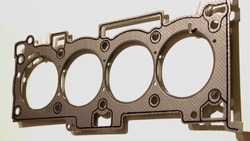 Closeup new engine cylinder head gasket with metal rings and sealing stripe, four cylinder car motor repair parts