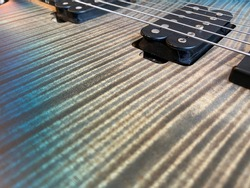 Closeup nickel stings and black pickup the blue burst  modern electric guitar satin finish patterned wood flame maple grain with copy space for text. music business concept.