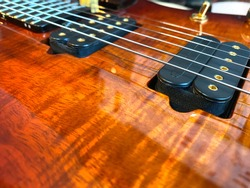 Closeup nickel stings and black pickup the orange guitar patterned wood Koa.