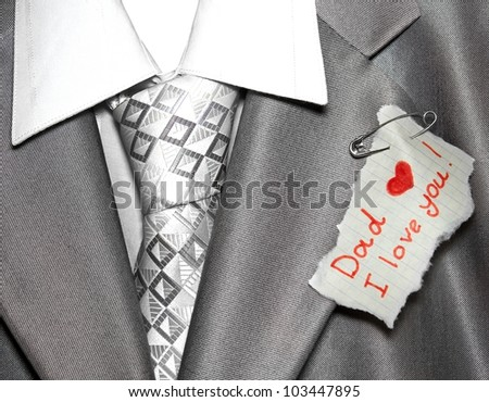 Closeup note for father pinned by a pin to his suit on father's day