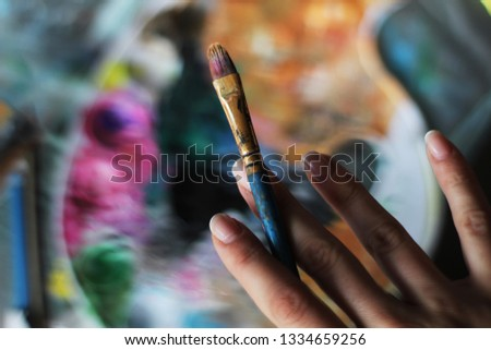 Closeup of a artist's hand while painting with Artists brush and acrylic paints on plastic palette. Vintage stylized photo of paintbrush closeup and artist palette.