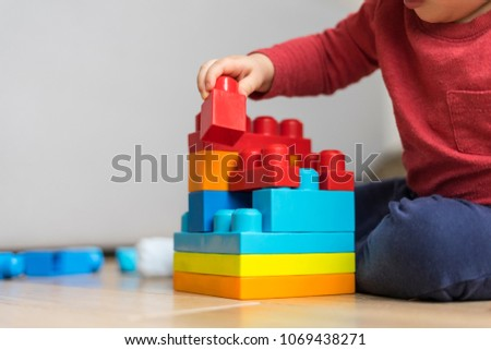 Closeup of a baby playing with colorful plastic bricks, selective focus. #1069438271