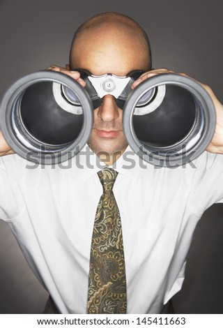 Closeup of a bald businessman looking through large binoculars against gray background
