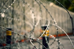 Closeup of a barbwire with defocused poles and tall gates on background. House security fencing.