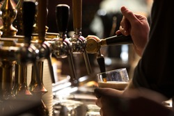 closeup of a bartender pouring a dark stout beer in tap with subject and focus on the right