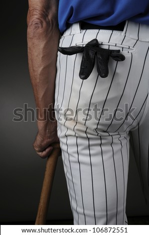 Closeup of a baseball player seen from behind and leaning on a wood bat. Man is unrecognizable with a batting glove in his pocket. Vertical format over a light to dark background.