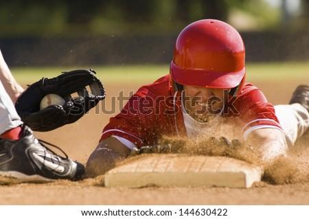 Closeup of a baseball player sliding to the base