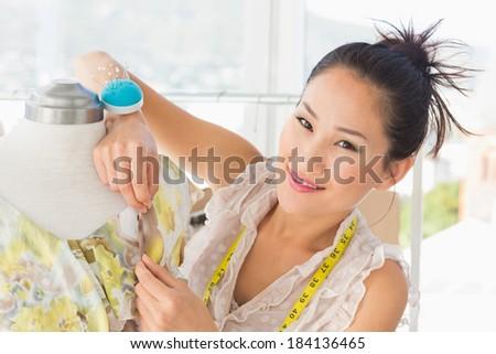 Closeup of a beautiful female fashion designer working on dress at the studio