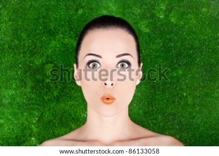 Closeup of a beautiful surprised woman beauty portrait in studio  grass background
