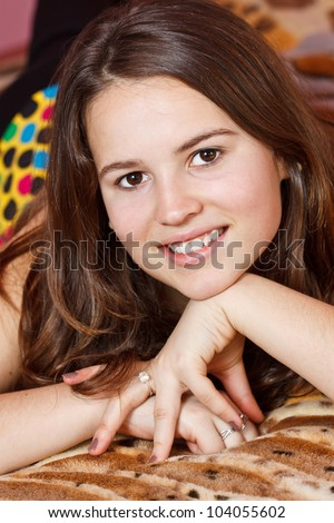 Closeup of a beautiful teenage girl with long brown hair, hands under her chin, lying on bed, smiling into camera