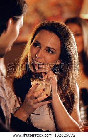Closeup of a beautiful woman at the bar talking with a guy